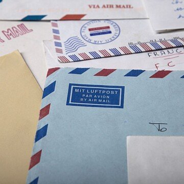 A collection of airmail envelopes scattered over a flat surface.