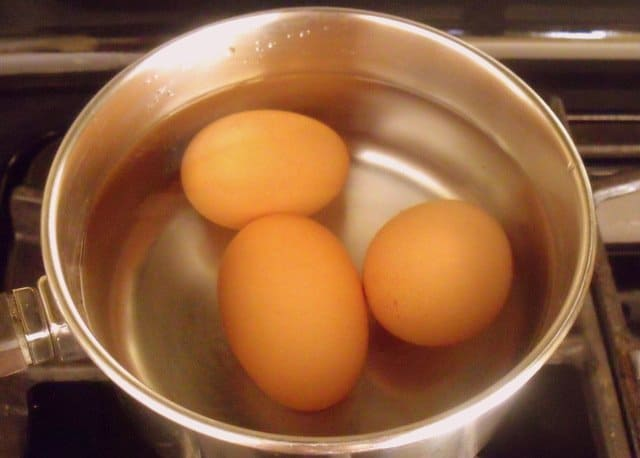 Three eggs covered in water for boiling in a silver saucepan