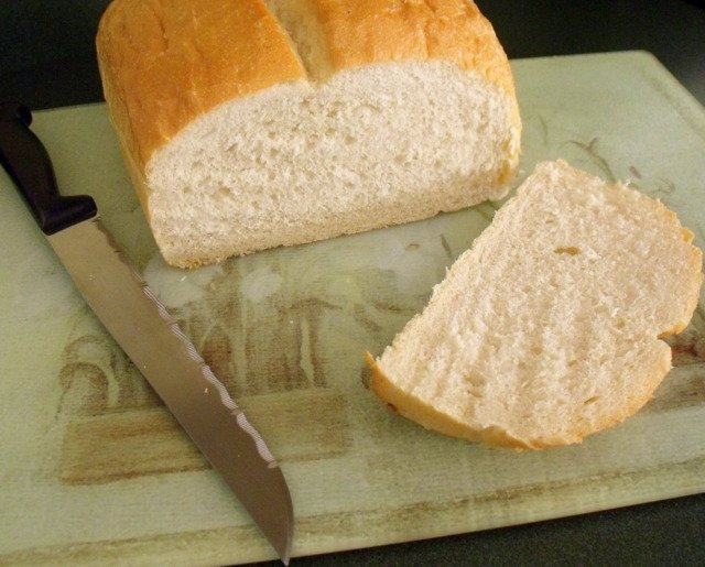 Sourdough bread loaf on a cutting board with a knife and one slice cut