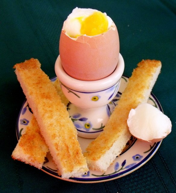 The top off a boiled egg in a cup with toast sticks