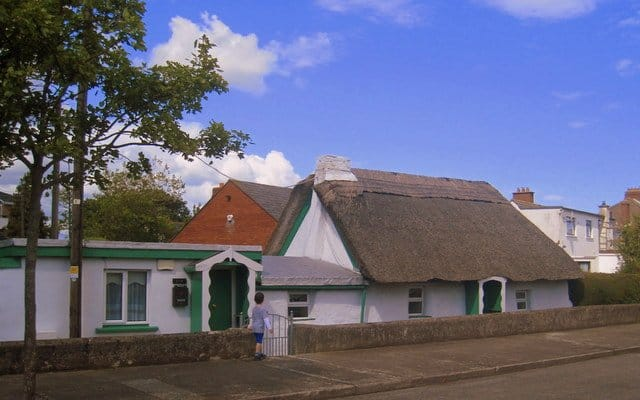 A white walled cottage with green paint trim and thatched roof