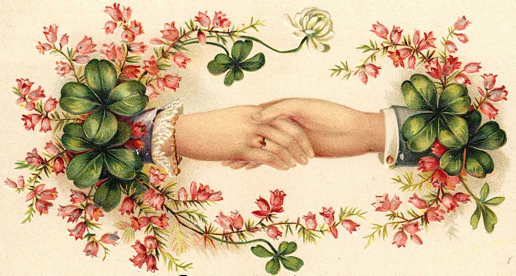 Four leafed clovers around two clasped hands