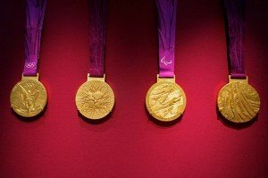 Four golden Olympic medals with purple ribbons against a red background