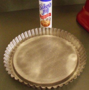 A metal flan dish with fluted edge sprayed with Baker's Joy