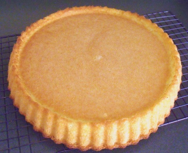 A sponge flan cooling on a wire rack with the raised edge visible.
