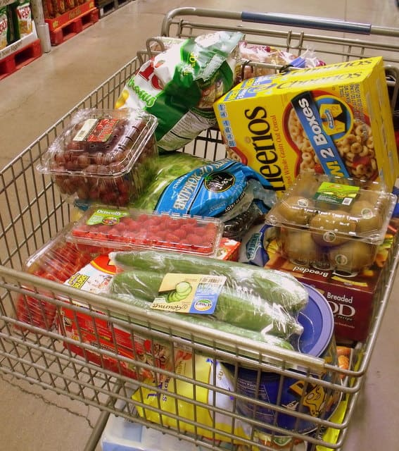 A shopping cart with fruit, cereal and vegetables