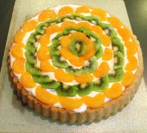 Orange and green fruit over cream in a sponge cake shell