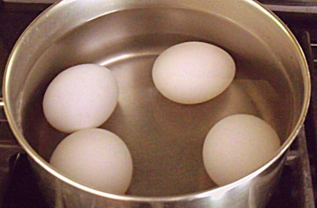 Four eggs covered in water in a silver saucepan