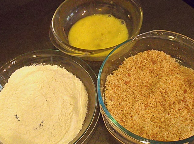 Egg wash, flour and breadcrumbs in thee bowls for coating Scotch eggs