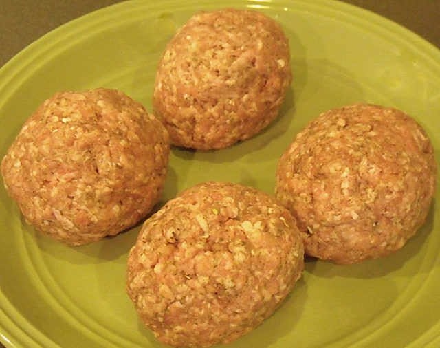 Four eggs covered in sausage meat on a green plate