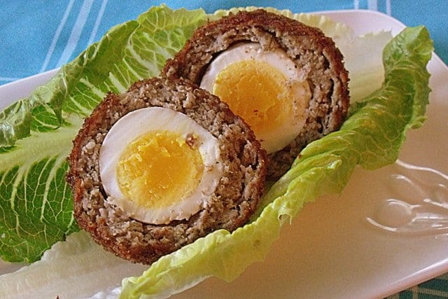 Two halves of an open Scotch egg on a bed of green lettuce on a white plate