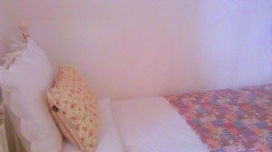 A floral pillow and patchwork quilt on a bed in an Irish cottage