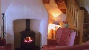 A wood burning stove with an chair inside an Irish thatched cottage