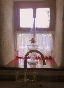 Lace curtained cottage window with an oil lamp on the window sill