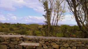 A stone wall outside a cottage looking toward the Connemara Mountains