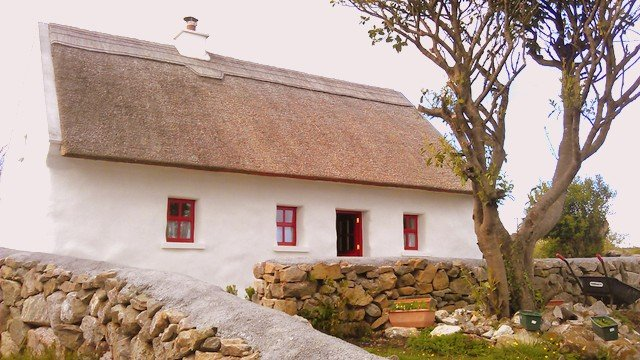 A white walled cottage with red door and window trim and thatched cottage roof
