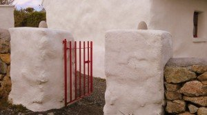Stone pillars painted white with a red gate outside an Irish thatched cottage
