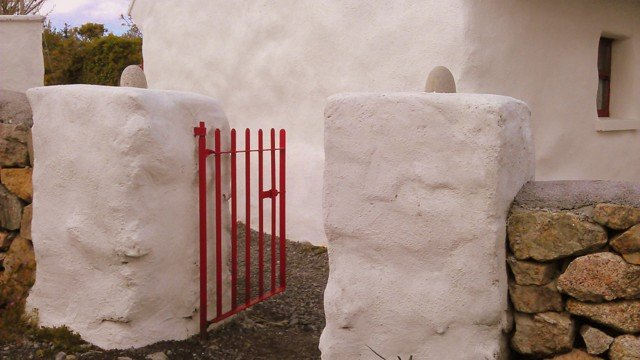 A red metal gate in a white stone wall