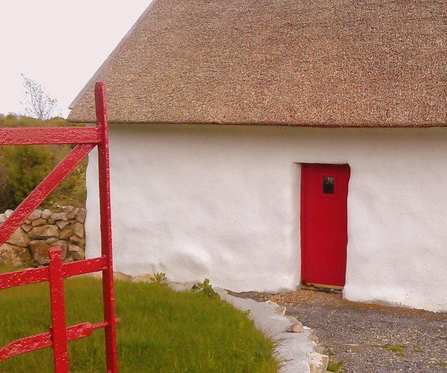 An Irish thatched cottage with white walls and a red door