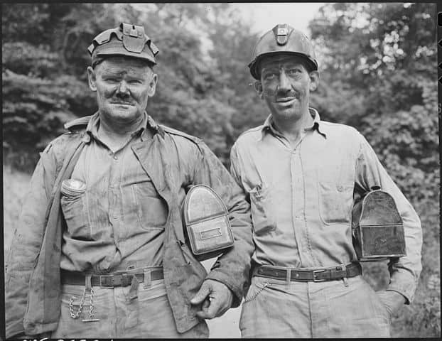 Black and white image of two coal miners with lunch pails