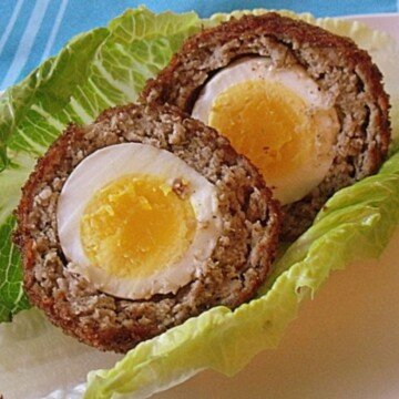 A scotch egg cut open to show the inner egg with yellow yolk and surrounded by sausage and bread crumb layers