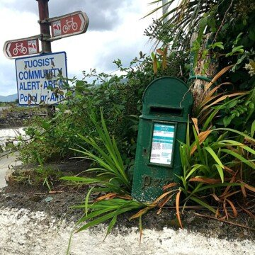 Small green post box on a wall beside a road sign