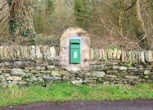 A green post or mail box on a stone wall in Ireland