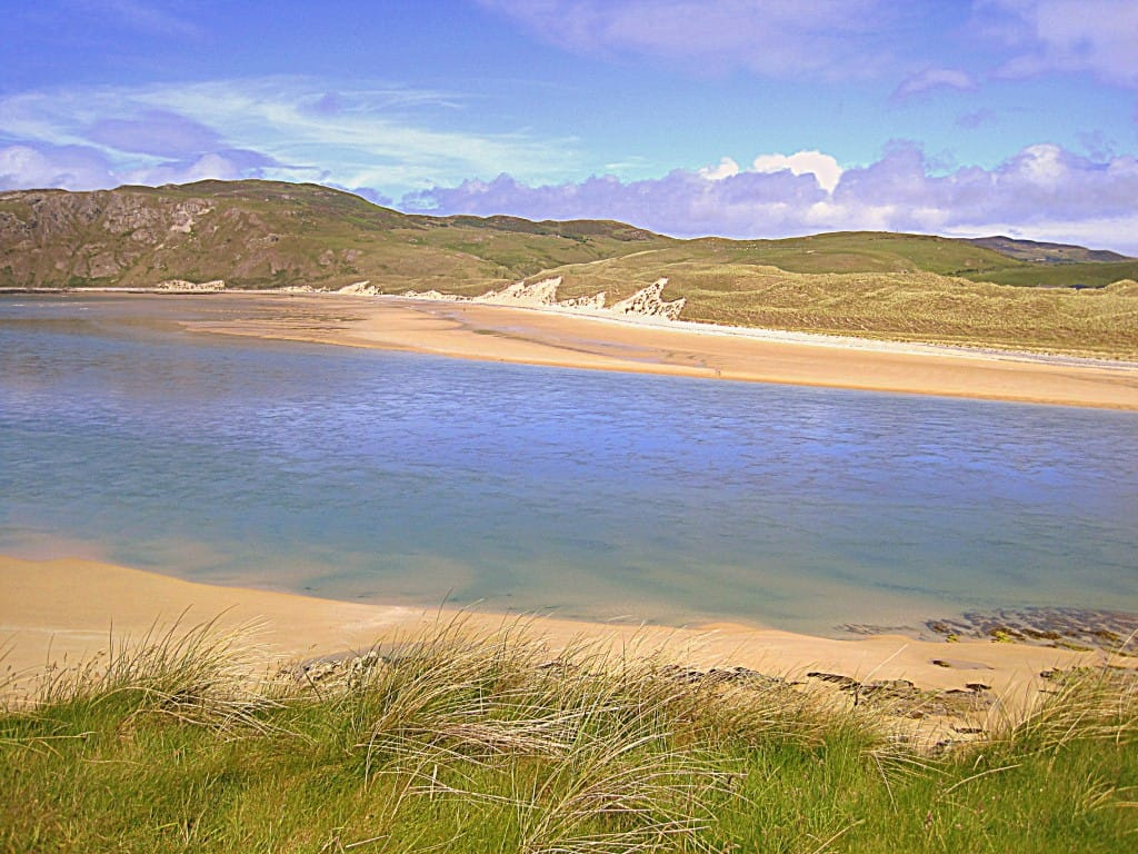 An inlet of water flowing between two sandy beaches