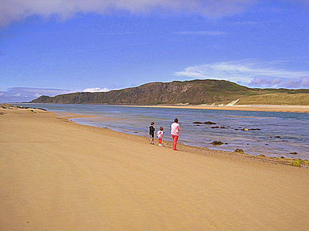 Children standing beside the water on a sandy beach with blue skies above