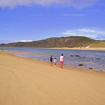 Three children by the waters edge on Doagh Beach County Donegal