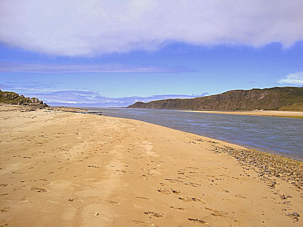 A sandy beach beside an inlet of water under a blue and cloudy sky