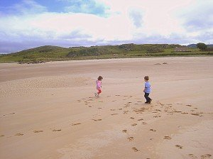 Two toddlers running on a sandy beach leaving footprints