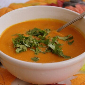 Orange carrot soup with chopped cilantro garnish in a white bowl with a spoon
