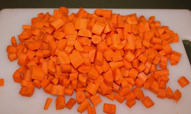A white chopping board with a pile of diced carrots for carrot and coriander soup