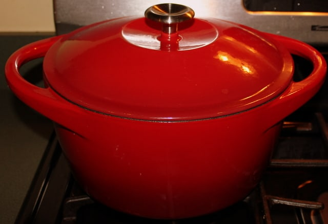 A red dutch oven on a stove top cooking carrot and coriander soup