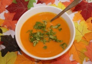 A bowl of orange carrot and coriander soup with fall leaves