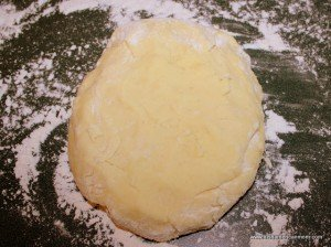 A ball of potato cake dough on a floured surface