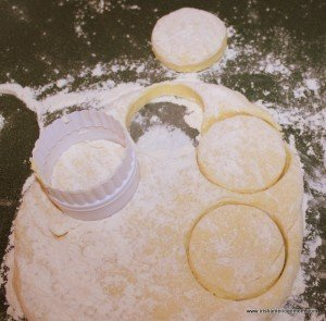 Using a cutter to shape round potato cakes from dough