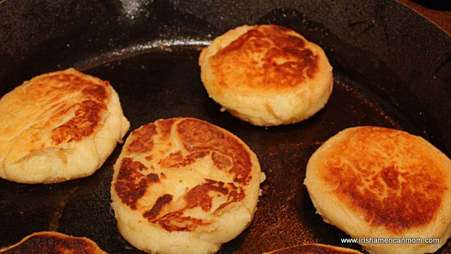 Golden crust on one side of Irish potato cakes frying in a cast iron pan