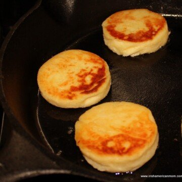Three Irish potato cakes frying in a cast iron skillet