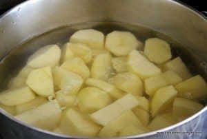 Peeled potatoes in a pot of water for Irish colcannon