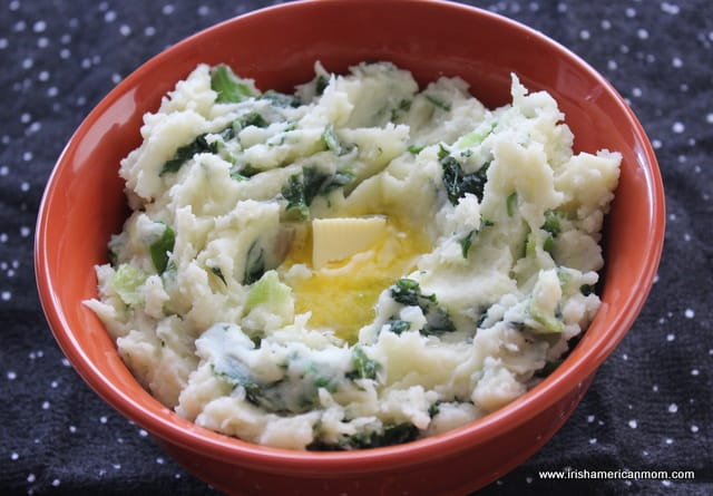 A knob of butter melting in a serving of Irish colcannon in an orange bowl
