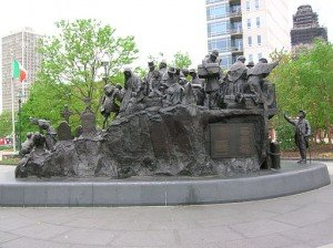 A view of the Irish Famine Memorial in Philadelphia with people carrying trunks and bundles beside gravestones