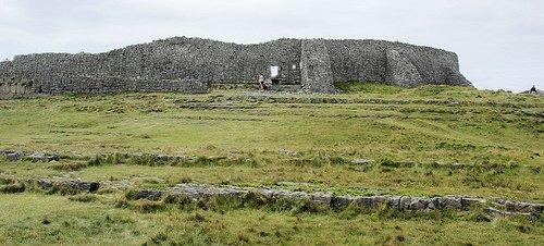 Stone fort walls in a green rocky field