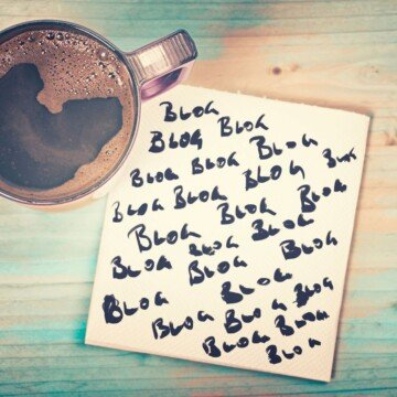 Cup of coffee beside a note with text on a green wooden surface