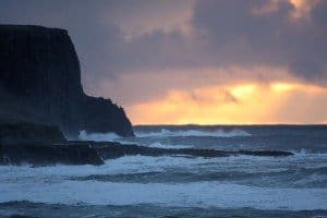 The sun setting over the waves beside the cliffs in Doolin County Clare