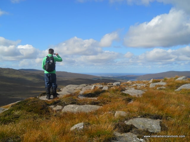 A hiker looks out over the mountain tops of County Donegal