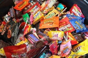A large bowl of candy with snickers, skittles, starburst, dots, whoppers