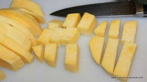 cutting a sliced rutabaga into cubes before boiling