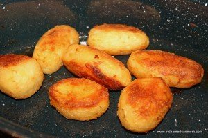 Seven crispy golden roasted potatoes in a black roasting pan